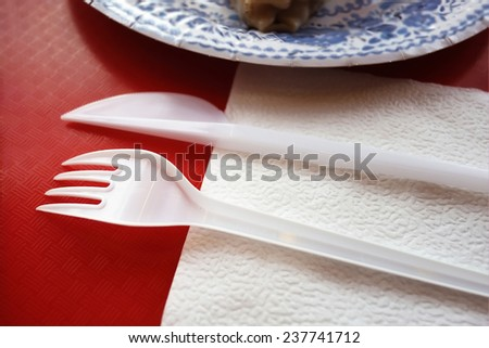 Overhead close up of disposable knife , fork and napkin laid on a red plastic tray, shot with shallow depth of field - stock photo