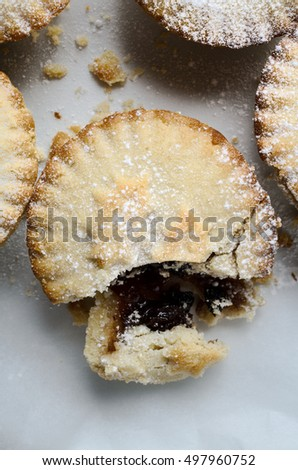 Overhead close up of one mince pie in a group, broken open as if partially eaten.  White Icing sugar sprinkles on pastry and surface.