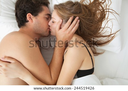 Overhead close up portrait of a young couple caressing laying in bed together in lingerie being romantic hugging and kissing. Couple in a relationship having sex, home interior lifestyle.