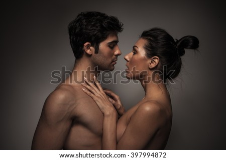 Overhead close up portrait of a young romantic couple hugging and kissing, laying down on a white bed, having sex and loving each other. Love and relationships lifestyle, interior bedroom. - stock photo