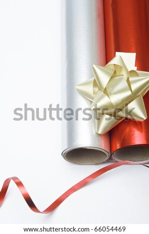 Overhead close up shot of two rolls of Christmas wrapping paper and a gold decorative rosette.  A swirl of shiny red ribbon is placed at the bottom of the frame.  Copy space to left.
