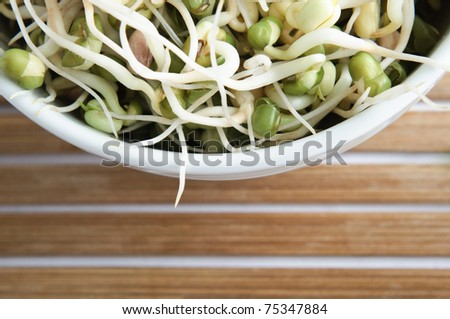 Overhead, cropped shot of a bowl of mung beansprouts, with horizontally slatted bamboo placemat in lower frame. - stock photo