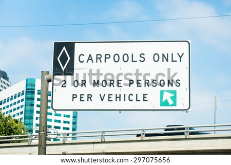 Overhead freeway carpool only sign with blue sky