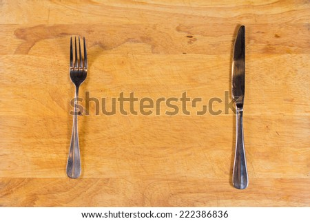 Overhead Image of Silver Fork and Knife on Wooden Surface - stock photo