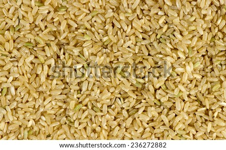 Overhead macro shot of uncooked raw brown rice background texture - stock photo