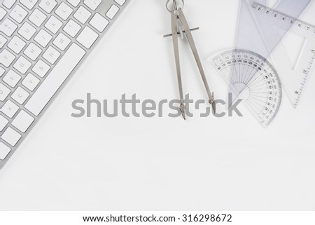 Overhead mock up of a white drafting table with computer keyboard, compass, protractor and angle. Horizontal format with copy space. - stock photo