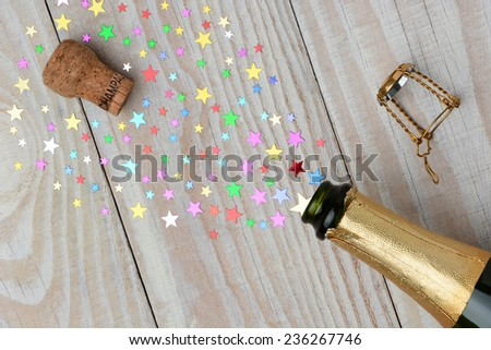 Overhead of a bottle of champagne with the cork popping on a rustic wood table. The spray from the bottle is stars of various sizes. With copy space it is perfect for New Years projects. - stock photo