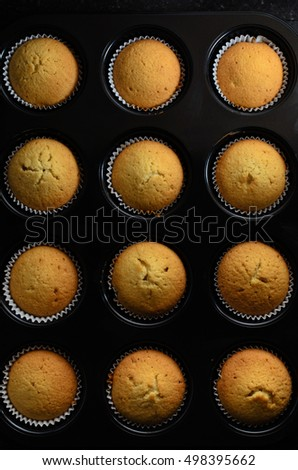 Overhead of a dozen golden cup cakes straight from the oven,  baked in paper cases and still inside black bun tin.