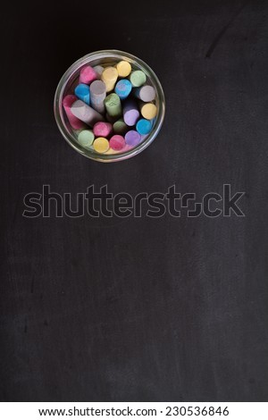 Overhead of chalkboard and jar of chalk and space for text - stock photo