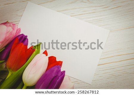 Overhead of colorful tulips and white card on wooden table - stock photo