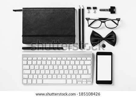 Overhead of essentials office objects in black and white./ Closeup of business objects in order on white desk.  - stock photo