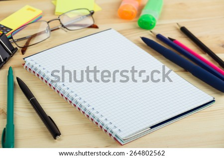 Overhead of open notebook with pen and glasses on a desk - stock photo
