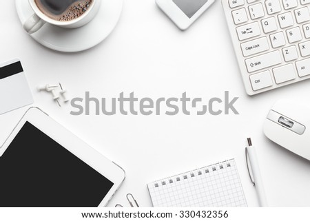 overhead of white office table with notebook, computer keyboard and mouse, tablet pc and smartphone. copy space - stock photo