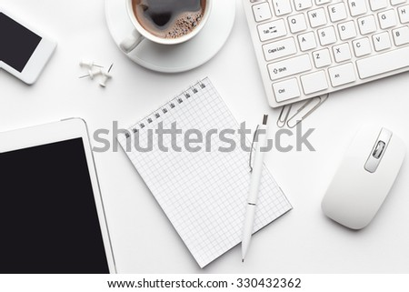 overhead of white office table with notebook, computer keyboard and mouse, tablet pc and smartphone - stock photo