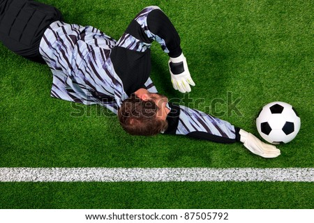 Overhead photo of a football goalkeeper diving to save the ball from crossing the goal line. - stock photo