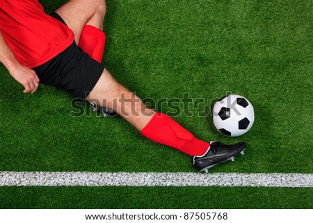 Overhead photo of a football or soccer player sliding in to save the ball going over the sideline - stock photo