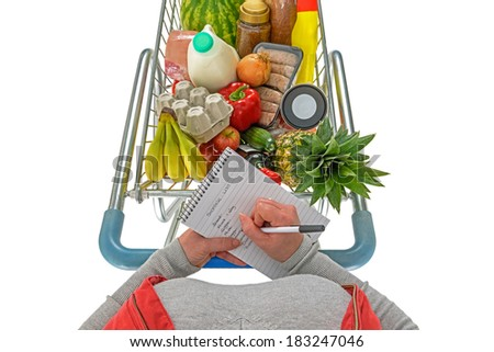 Overhead photo of a woman checking her shopping list with a trolley full of fresh food, isolated on a white background. - stock photo