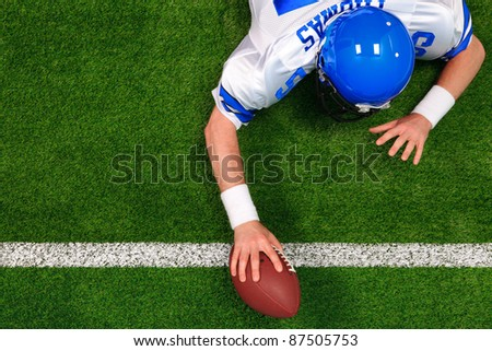 Overhead photo of an American football player making a one handed touchdown. The uniform he's wearing is one I had made using my name and does not represent any actual team colours. - stock photo