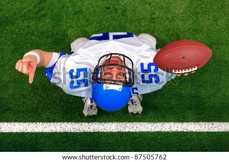 Overhead photo of an American football player making a touchdown celebration looking up in the air with his finger raised. The uniform he's wearing does not represent any actual team colours. - stock photo