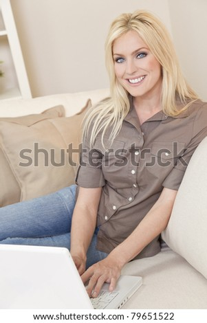 Overhead photograph of beautiful young woman at home sitting on sofa or settee using her laptop computer and smiling - stock photo