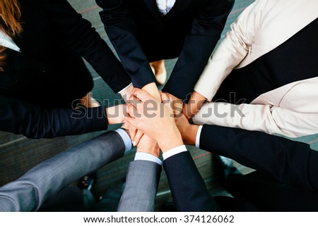 Overhead picture of business people joining hands - stock photo