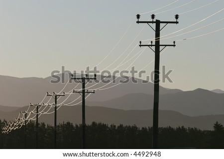 Overhead power lines in a remote area of Canterbury, New Zealand. Southern Alps in the background. - stock photo