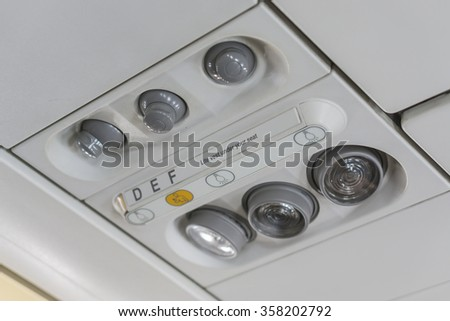 Overhead seat controls of a commercial aircraft - air conditioning nozzles, reading lamps, no-smoking and seat belt on signs. Three seats.selecttive focus. - stock photo