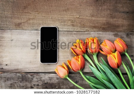 Overhead shot a blank cell phone with a bouquet of orange and yellow tulips over a wood table. Flat lay top view style.