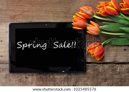 Overhead shot a tablet with text Spring Sale and a bouquet of orange and yellow tulips over a wood table. Flat lay top view style.