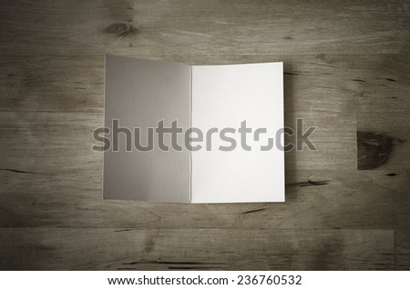 Overhead shot of a blank greeting card, lying face upwards and opened on a wooden planked table.  Low saturation and vignetted vintage style. - stock photo