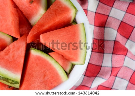 Overhead shot of a bowl full of watermelon wedges on a checkered table cloth. Horizontal format. Half the bowl is shown, offset to one side of the frame. - stock photo