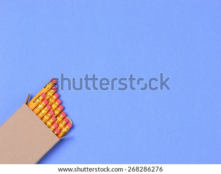 Overhead shot of a box of new yellow pencils in on a blue background. The pencils are in the lower left corner leaving room for your copy. - stock photo