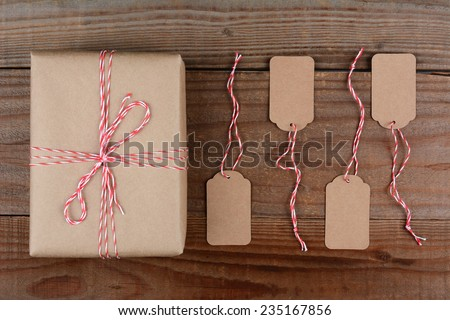 Overhead shot of a Christmas Package wrapped in plain brown paper and tie with red and white string. Four blank tags are next to the gift on a dark rustic wood table. - stock photo