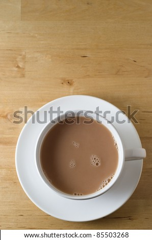 Overhead shot of a cup of tea, with saucer on old, scratched light wooden table with copy space in top frame.  Vertical (portrait) orientation. - stock photo