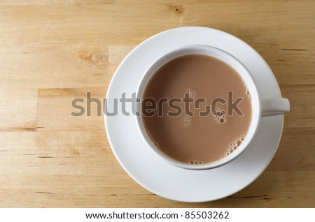 Overhead shot of a cup of tea, with saucer on old, scratched light wooden table with copy space to left.  Landscape (horizontal) orientation. - stock photo