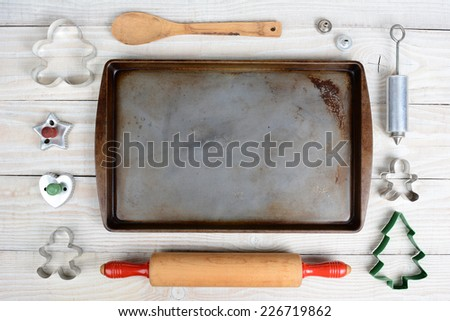 Overhead shot of a group of items for baking Christmas Cookies surrounding an empty cookie sheet. Horizontal format on a  rustic wood kitchen table.  - stock photo