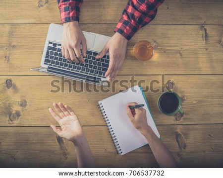 Overhead shot of a man and a woman drinking tea and working at a desk with laptop and notepad