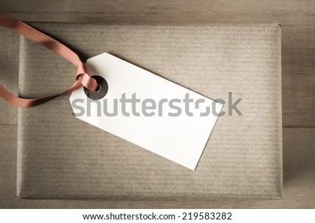 Overhead shot of a neatly wrapped oblong gift in brown paper.  Parcel tag and undersaturated red satin ribbon face upwards to provide copy space for a message.  Vintage style. - stock photo