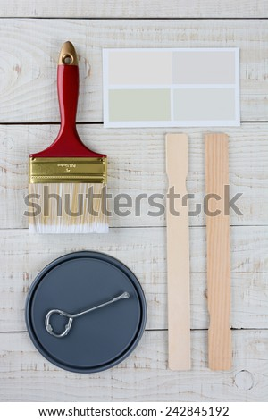 Overhead shot of  a paint can lid, opener, color samples, stir sticks and paint brush on a rustic wooden surface. Vertical format with copy space. - stock photo