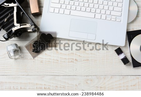 Overhead shot of a photographers workspace. A vintage film camera, film, negatives and the equipment to transfer analog images to digital. The items are on a white rustic table with copy space. - stock photo