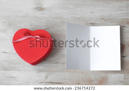 Overhead shot of a red heart-shaped gift box with ribbon bow, and a blank, opened greeting card. Both set on a light woodplank table.  Processed to give a very light, whitened feel. - stock photo