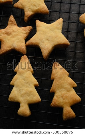 Overhead shot of a selection of Christmas biscuits in tree and star shapes, freshly baked and placed on a black wire cooling rack.