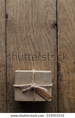 Overhead shot of a simple brown string tied gift box or parcel on a rustic old wood plank table.  A  vintage style blank gift tag faces upwards. - stock photo