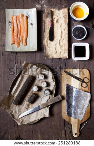 overhead shot of a sliced roll of fried hosomaki sushi and ingredients on table - stock photo