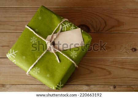 Overhead shot of a wrapped green Christmas gift parcel with snowflake pattern, tied with string.  Blank label faces upwards to provide copy space.  Set on an old, worn wooden table. - stock photo
