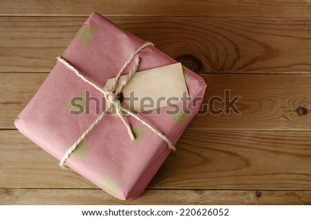 Overhead shot of a wrapped pink paper parcel with heart pattern, tied with string.  Blank label faces upwards to provide copy space.  Set on an old, worn wooden table. - stock photo
