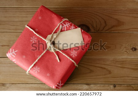 Overhead shot of a wrapped red Christmas parcel with snowflake pattern, tied with string.  Blank label faces upwards to provide copy space.  Set on an old, worn wooden table. - stock photo