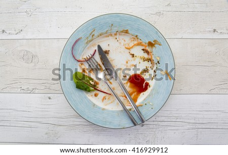 Overhead shot of an empty plate with leftovers from a meal on a white wooden backround - stock photo