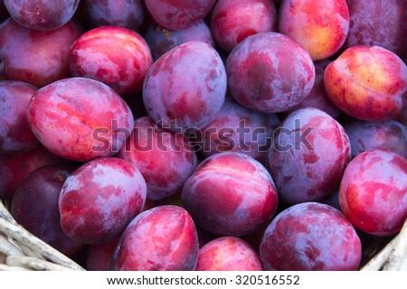 Overhead shot of basket of juicy plums - stock photo