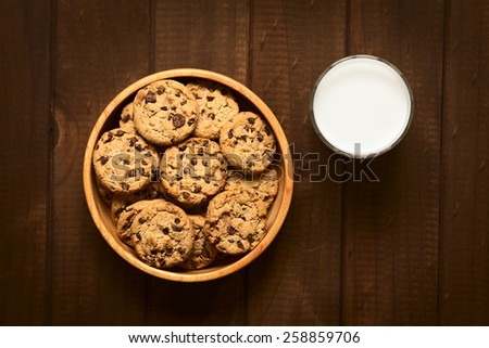 Overhead shot of chocolate chip cookies in wooden bowl with a glass of cold milk on the side photographed on wood with natural light - stock photo